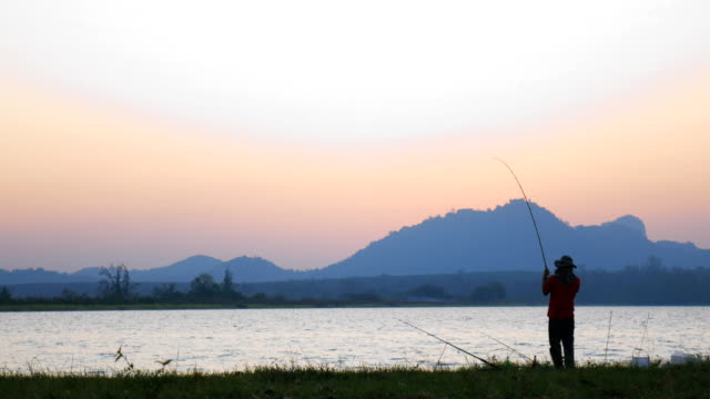 A man to fishing on silhouette evening time A man to fishing on silhouette evening time with lake and mountain background fishing rod stock videos & royalty-free footage