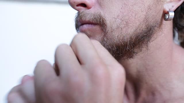 vídeos de stock e filmes b-roll de man touches his beard on white background - puxar cabelos