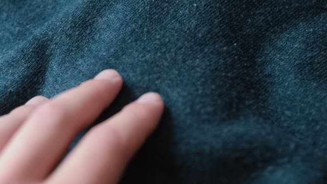 Man touching a smooth, blue acrylic fabric in a textiles shop