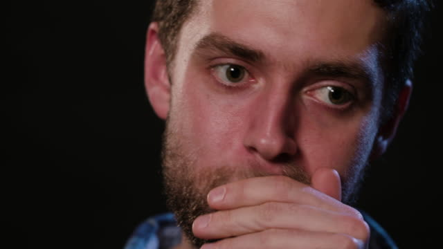 A Man Touching his Lips Against a Black Background A young man touching his lips and beard against a black background. Close-up Shot beard stock videos & royalty-free footage