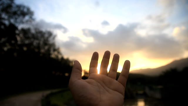 Man touching the sunlight by hand over sunset sky background. - vídeo
