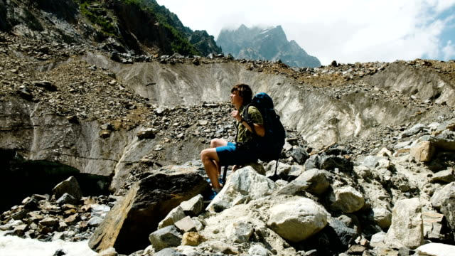 man tourist is resting in the mountains, drinking water and enjoying the view - trekking sul ghiaccio video stock e b–roll