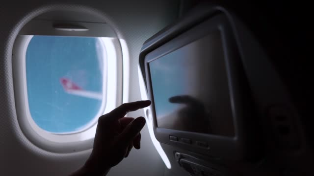 Man tourist on a plane. Close-up shot of a man using built-in display on a plane during flight, watching movies to kill time. Touch screen display in plane seat. arts culture and entertainment stock videos & royalty-free footage