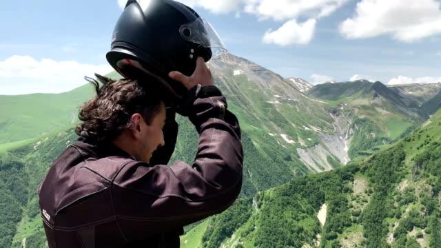 mann tourist setzen von motorradhelm und schauen auf der sicht in grünen kaukasischen bergen reisekonzept atem - kopfbedeckung stock-videos und b-roll-filmmaterial