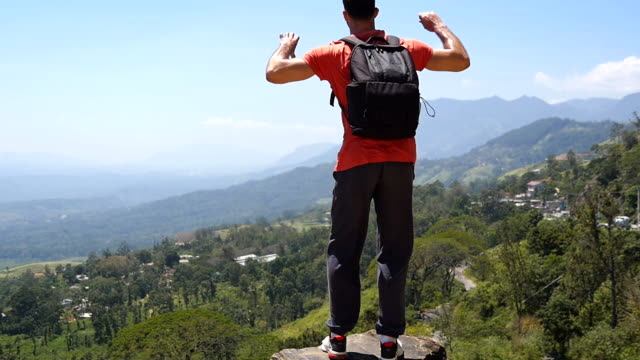 Man tourist with backpack stands to the edge of beautiful canyon and outstretched arms up. Male hiker reaches up top of mountain and raises hands up. Young backpacker enjoys picturesque landscape.