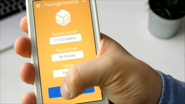 vídeos de stock, filmes e b-roll de homem rastreia seu pacote usando o aplicativo de smartphone - correio correspondência