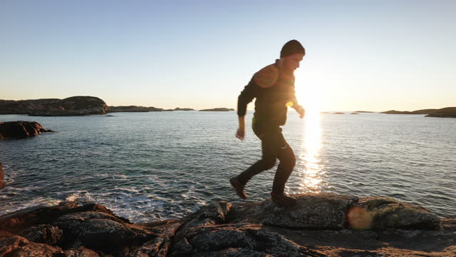 Man trail running on a rocky coast during a winter sunset