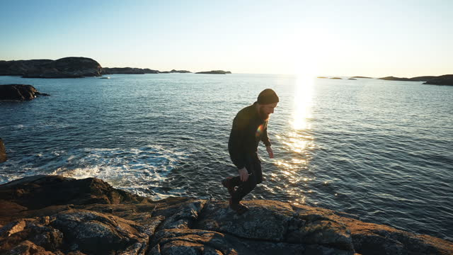 Man trail running on the rocks by a fjord, in Norway