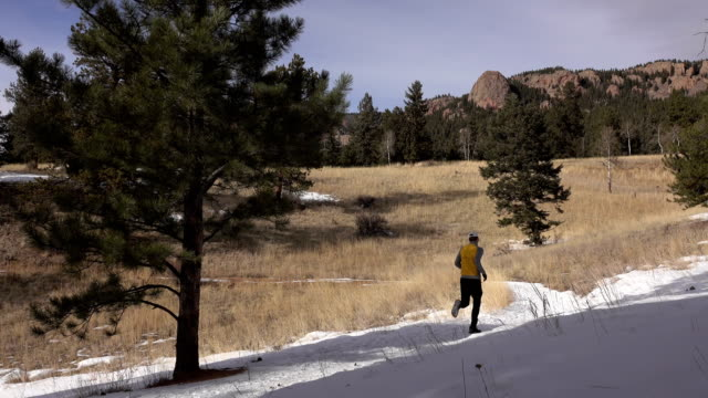 Man trail running snowy path Staunton State Park forest Colorado Rocky Mountain winter video