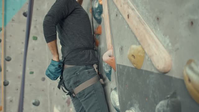 Man training at a climbing gym applies magnesium to her hands,Slow motion