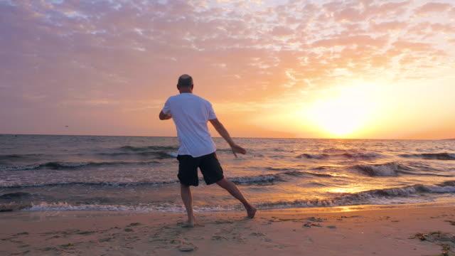 Man training martial art Taijiquan on sea beach and evening sunset landscape