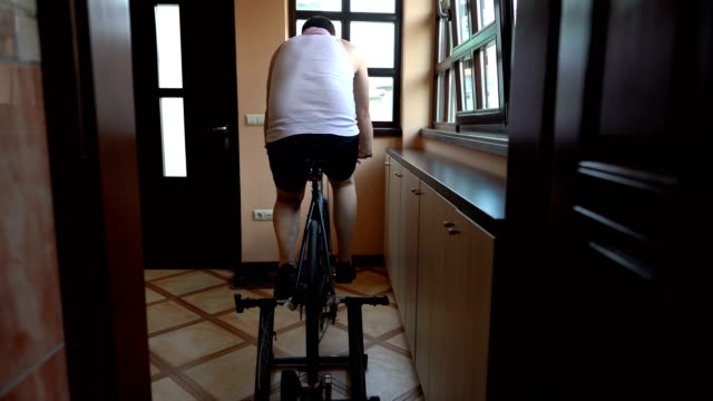 Man training on cycle home trainer Man training on cycle home trainer exercise bike stock videos & royalty-free footage
