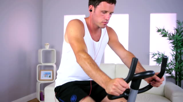 Man Training On Exercise Bike And Listening To Music Stock