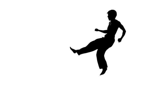vídeos y material grabado en eventos de stock de hombre de entrenamiento de taekwondo o karate salto, pierna en alto y puño punzón aislado sobre fondo blanco, silueta, cámara lenta - artes marciales
