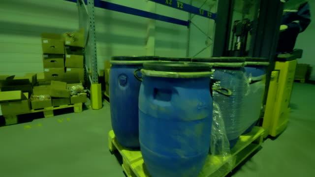 A man transports plastic barrels on a forklift. video