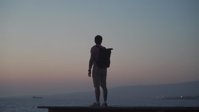 Man traveler with backpack admires the view of sunset and the mediterranean sea from wooden pier on island of cyprus. Freedom concept. Wanderlust travel, male enjoying sunset, solo traveler