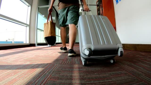 man traveler with luggage walking through airport terminal - airports stock videos & royalty-free footage