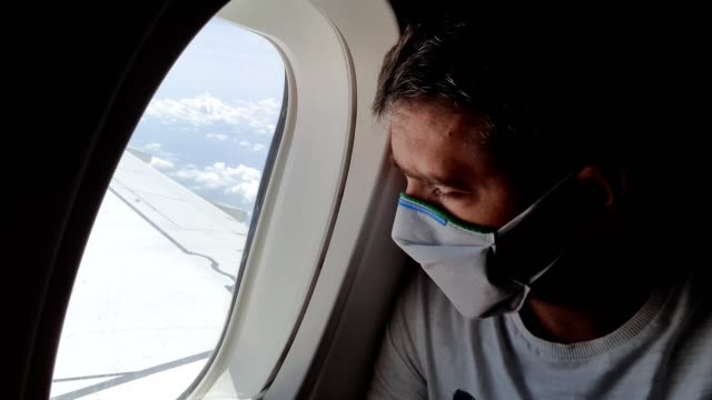 Man traveling by plane during coronavirus epidemic Young man with protective mask is looking worried through the window of the airplane. travel stock videos & royalty-free footage