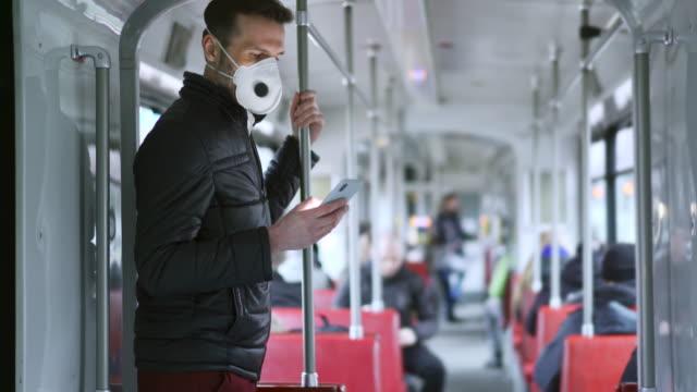 uomo che viaggia in tram indossando una maschera protettiva durante l'epidemia di coronavirus in europa usando il telefono - autobus video stock e b–roll
