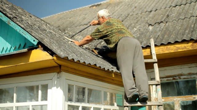 A man tries to fix the roof. He is standing on the stairs near the house video