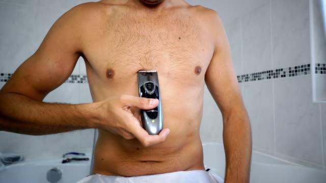 man trimming chest hair in bathroom - torace umano video stock e b–roll