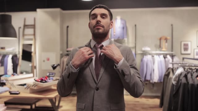 man trying business suit at clothing store video