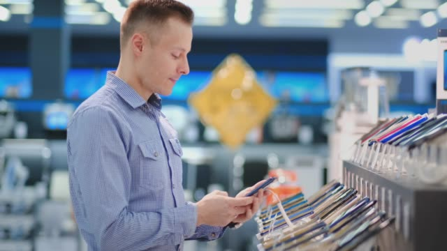 Man trying out new smart phone. Tech store interior Man trying out new smart phone. Tech store interior electronics store stock videos & royalty-free footage