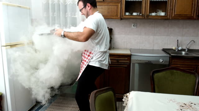 man trying to make dinner - bruciato video stock e b–roll