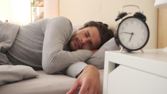 man vrida väckarklocka på morgonen - alarm clock bildbanksvideor och videomaterial från bakom kulisserna