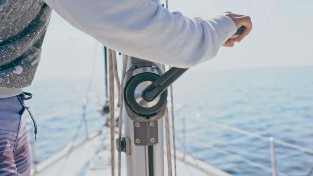 4K Man turning crank, adjusting rigging on sunny sailboat, real time 4K Man turning crank, adjusting rigging on sunny sailboat. MS, real time. crank mechanism stock videos & royalty-free footage
