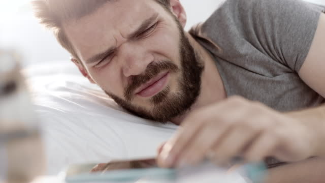 Man turning off alarm on smartphone and keep sleeping Bearded man turning off alarm on smartphone and keep sleeping in the morning instrument of time stock videos & royalty-free footage
