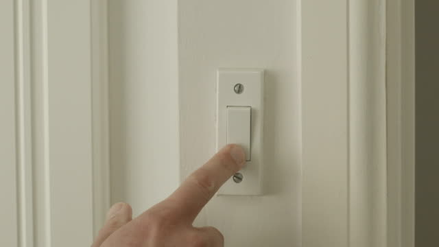 man turning on multiple light switches - componente elettrico video stock e b–roll