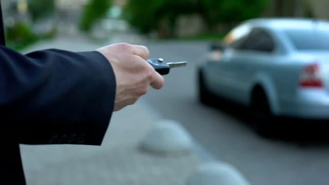 man vänder på billarm, säkerhetskoncept, risk för kapning bil parkerad på gatan - stationär bildbanksvideor och videomaterial från bakom kulisserna