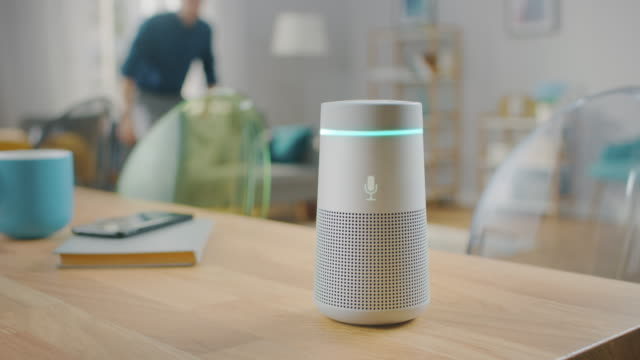 man turns on smart speaker that activates artificial intelligence assistant. - ai stock videos & royalty-free footage