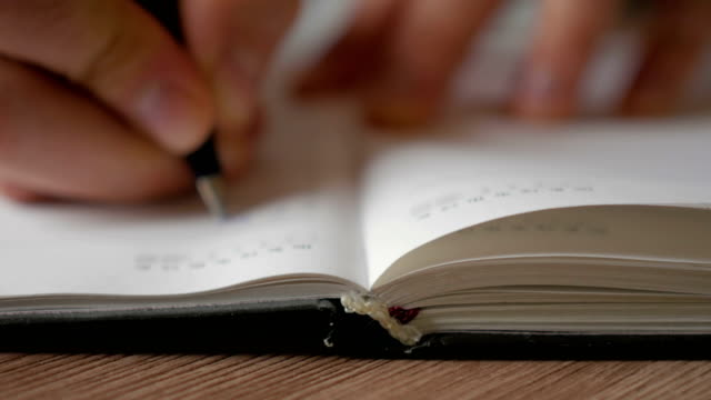A man turns over the blank pages of the diary. Businessman makes notes in a notebook.