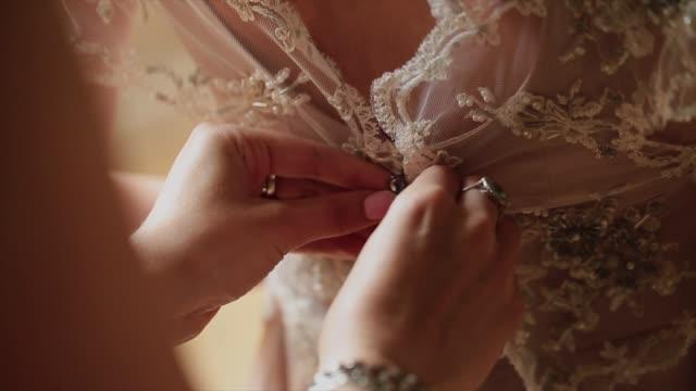 Man tying a corset on the bride's wedding dress video