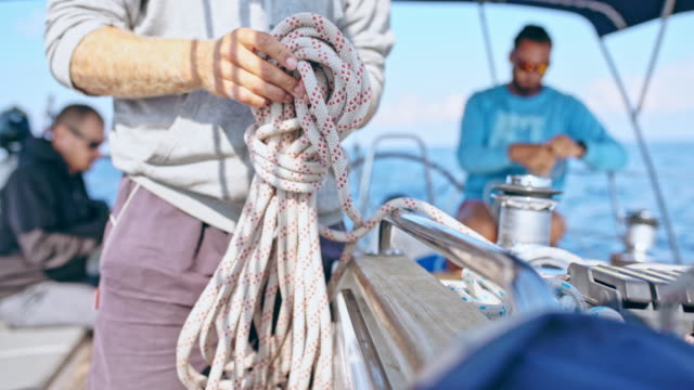 4K Man tying rigging rope on sailboat, real time 4K Man tying rigging rope on sailboat. CU, LR pan, real time. mast sailing stock videos & royalty-free footage