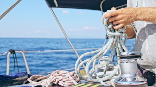 4K Man tying rigging rope on sunny sailboat, real time