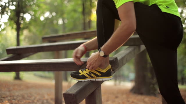 Man tying running shoes in the park. Optical focus is on the shoe. Man tying running shoes in the park. Optical focus is on the shoe. ankle stock videos & royalty-free footage