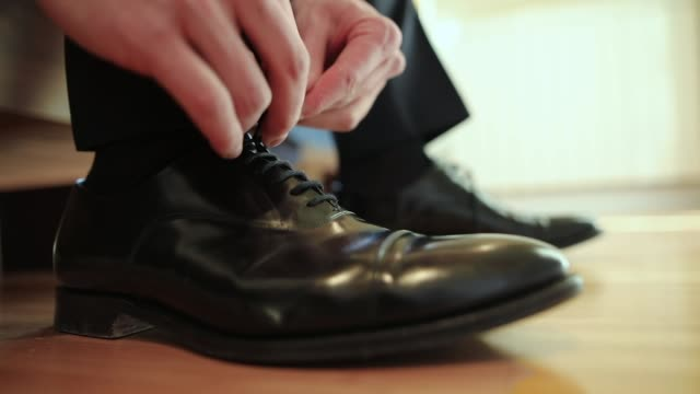 Man tying shoe laces close-up video