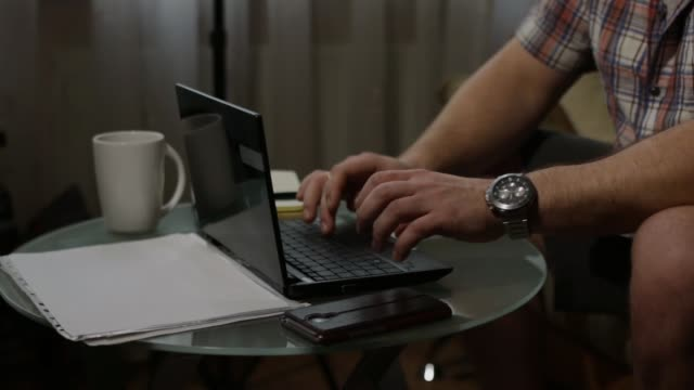 Man typing at home desk