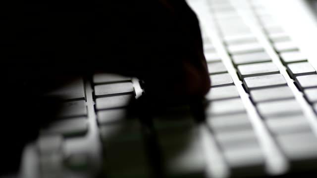 człowiek pisanie na komputerze klawiatury - haker komputerowy filmów i materiałów b-roll