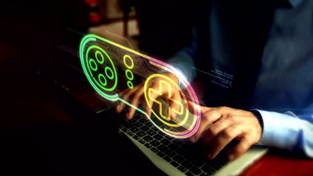 Man typing on keyboard with game pad symbol hologram