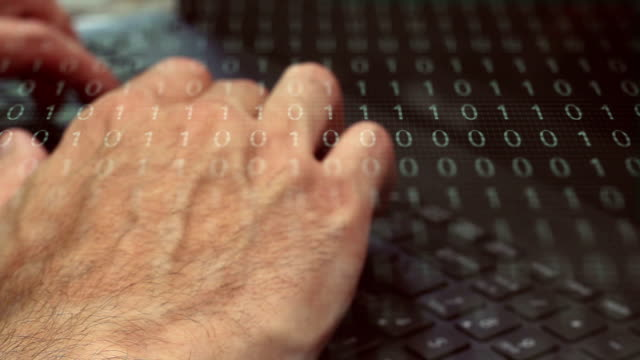 Man typing on laptop with binary code overlay - software concept video