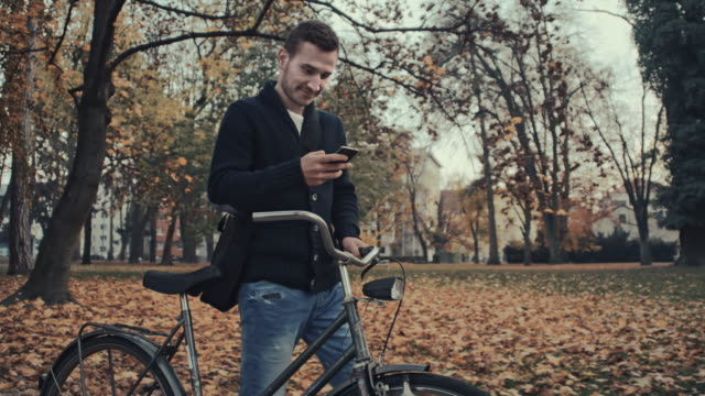 Man typing sms while pushing a bicycle video