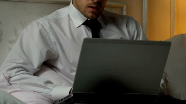 Man typing weekly report on laptop pc, busy journalist working on article in bed