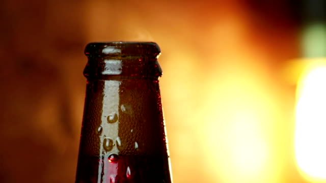 man uncork a bottle of beer with foam with ice frozen drops, on gold brown background, fun and nutrition drink man uncork a bottle of beer with foam with ice frozen drops, on gold brown background, fun and nutrition food and drink lager stock videos & royalty-free footage