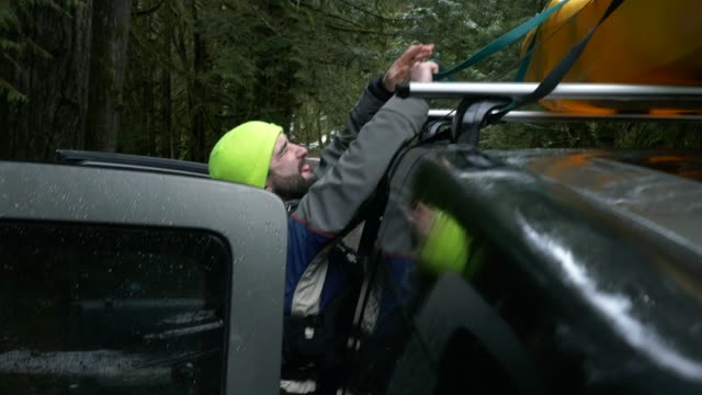 man unloading kayaking from car rack for extreme adventure - вешалка стоковые видео и кадры b-roll