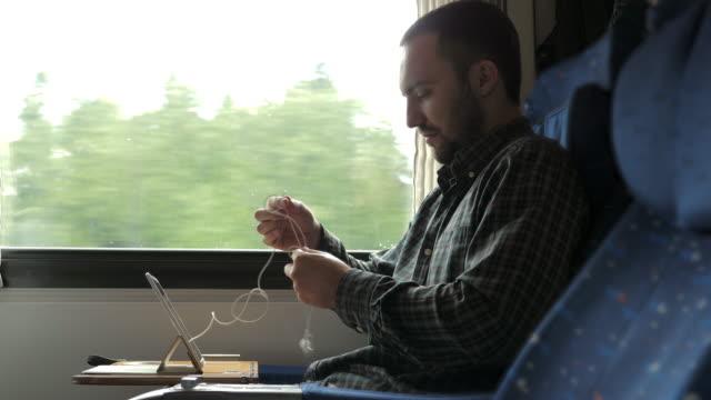 vidéos et rushes de l'homme démêlent les petits écouteurs blancs sur un voyage de train - ligoté