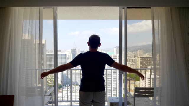 man unveil curtain and looking out of window in hawaii in 4k slow motion 60fps - budzić się filmów i materiałów b-roll